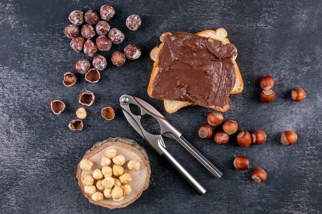Nocciole sgusciate con pane spalmato di cacao, schiaccianoci, pezzo di legno vista dall'alto su un tavolo di pietra scura
