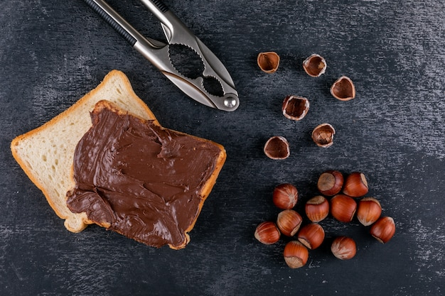 Shelled hazelnuts with cocoa spread bread, nutcracker top view on a dark stone table