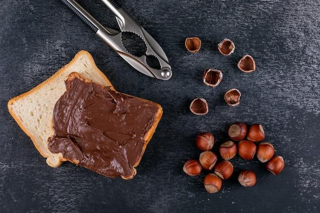 Nocciole sgusciate con pane spalmato di cacao, vista dall'alto di schiaccianoci su un tavolo di pietra scura
