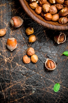 Shelled hazelnuts with leaves in a bowl . on a wooden.