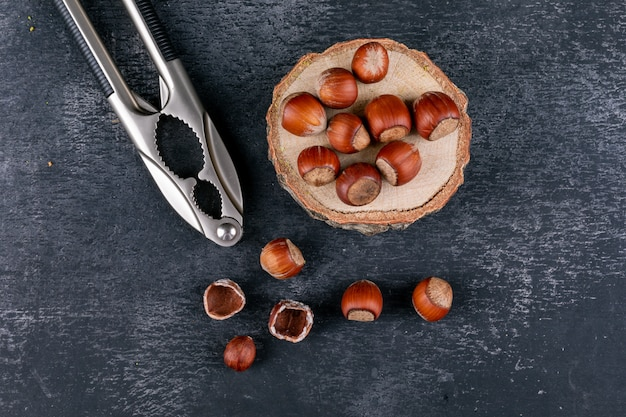 Shelled hazelnuts with nutcracker and piece of wood top view on a dark stone table