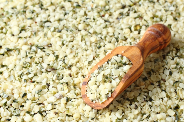 Shelled hemp seeds in wooden scoops, one of the superfoods.