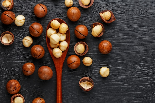 Shelled macadamia nut and peeled macadamia nut on a black textural background in a wooden spoon