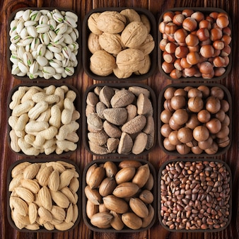 배경 나무 테이블에 셸된 견과류입니다. 구성 건강 식품: 피칸, 헤이즐넛, 호두, 피스타치오, 아몬드, 마카다미아, 땅콩, 소나무, 브라질.