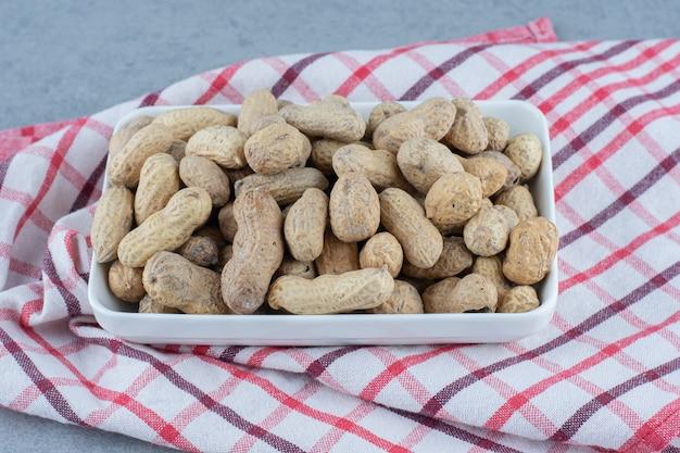 Очищенный арахис в миске, на полотенце, на мраморном столе.