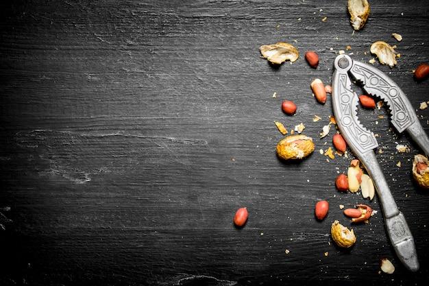 Очищенный арахис в скорлупе и щелкунчик. на черном деревянном столе