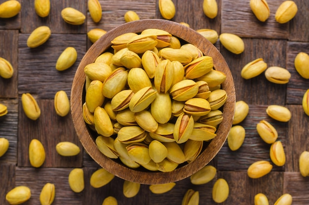 Shelled pistachios, roasted nuts with saffron in wooden bowl, top view.