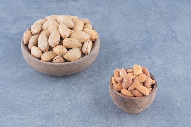 Shelled and unshelled almonds on the marble background.