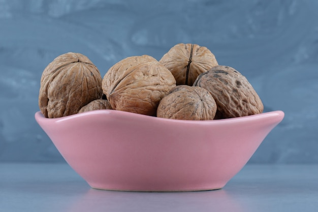 Shelled walnut in the bowl, on the marble table.