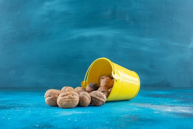 Очищенные грецкие орехи в ведре, на синем столе.
