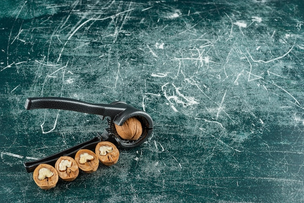 Shelled walnuts with nut cracking tool on marble table.