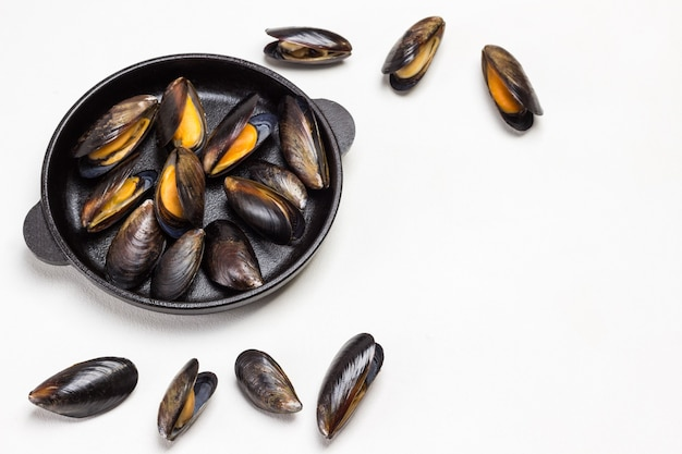 Shellfish mussels in frying pan. mussels are scattered on table. flat lay.