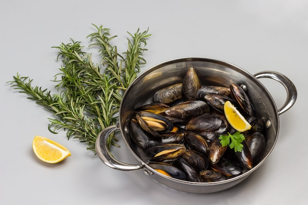 Shellfish mussels in frying pan. rosemary and lemon on table. shellfish seafood. flat lay