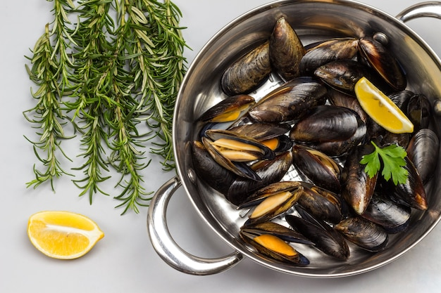 Shellfish mussels in frying pan. rosemary and lemon on table. shellfish seafood