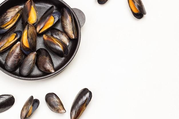 Моллюски мидии в сковороде. по столу раскиданы мидии. плоская планировка.