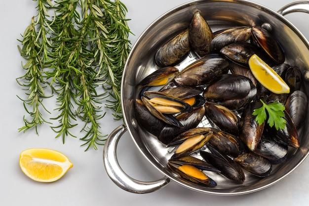 Моллюски мидии в сковороде. розмарин и лимон на столе. морепродукты из моллюсков
