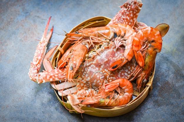 Тарелка из морепродуктов из моллюсков с дымящимися креветками, креветками и крабами на темном фоне