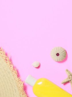 Shells, a bottle of sunscreen lotion, a fragment of a straw hat on pink flat lay