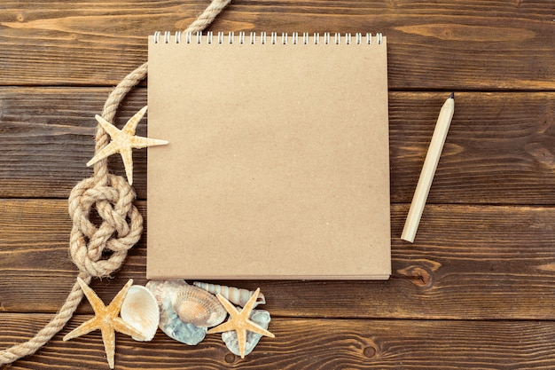 Shells and notepad on wooden table, top view with copy space