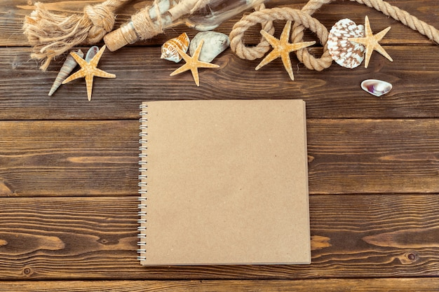 Shells and notepad on wooden table in top view with copy space