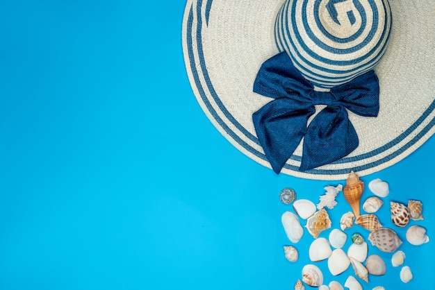Shells and summer hat with blue stripes and bow