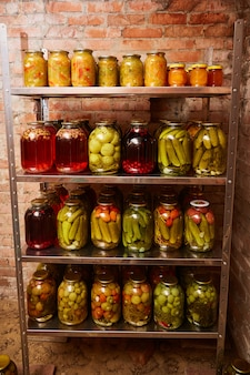 Shelves with homemade pickled vegetables and stewed fruit. vertical shot.