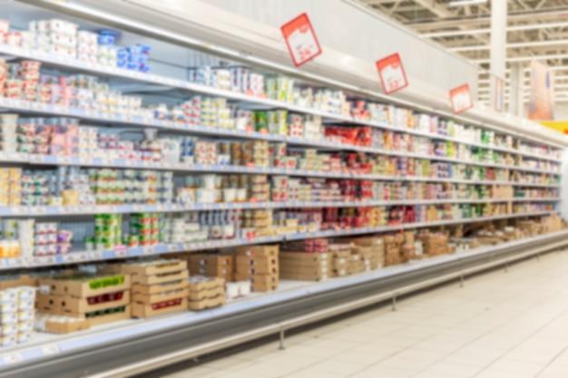 Полки с продуктами в большом супермаркете. размытый.