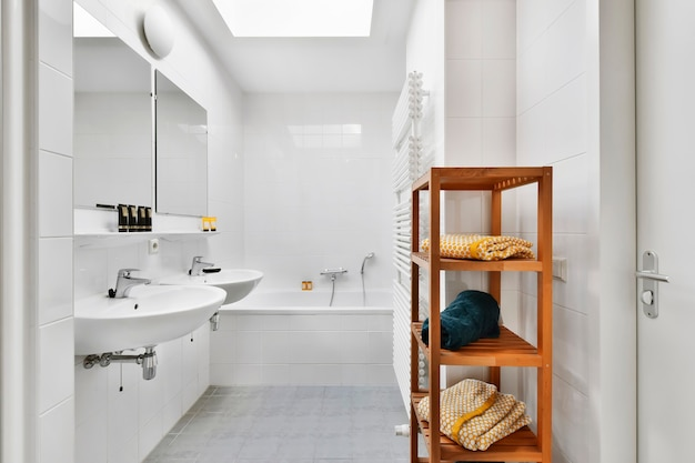 현대 아파트의 밝은 욕실에 거울과 욕조가있는 싱크대 근처에 수건과 건조대가있는 선반