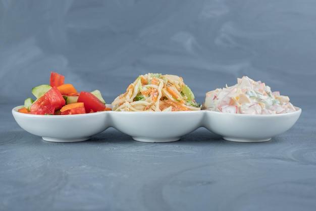 Insalate di pastore, olivier e verdure miste porzionate in un piatto da portata su un tavolo di marmo.