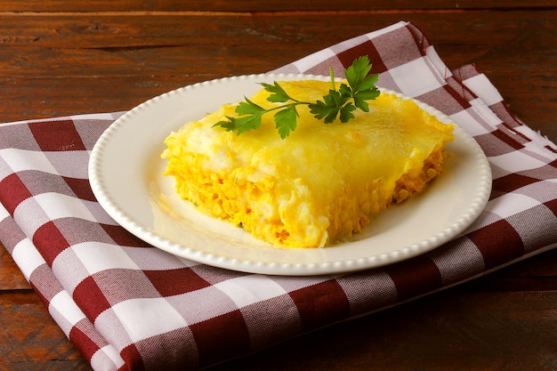 Shepherd's pie (escondidinho of chicken) is a very popular dish in the states of northeast brazil. made with sun-dried meat or shredded chicken, topped with cassava puree. top view