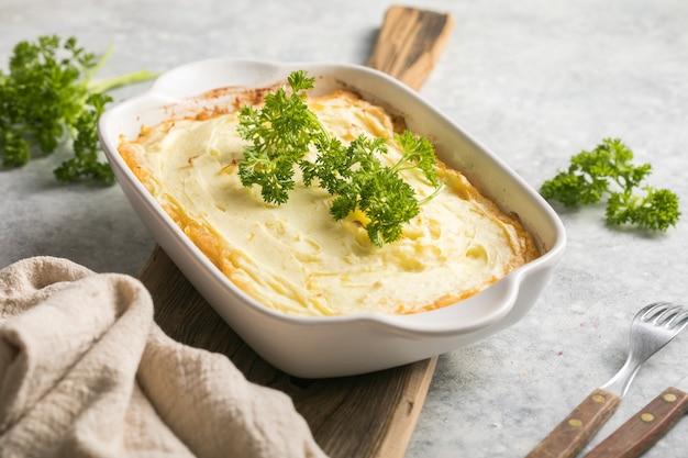Пирог овчарки с говяжьим фаршем, картофелем и сыром на деревянных фоне, вид сверху, копией пространства. традиционная домашняя ирландская запеканка