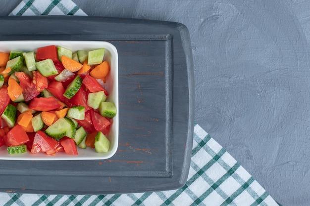 Салат пастыря, смешанный с ломтиками моркови на темно-синем блюде на мраморном фоне.