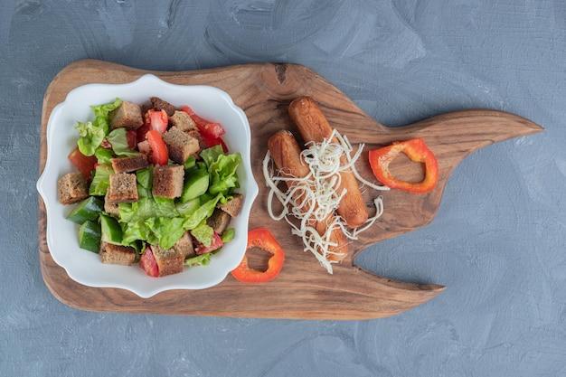 Insalata di pastore, salsicce arrosto, stringhe di formaggio e fette di pepe su una tavola di legno su una superficie di marmo.