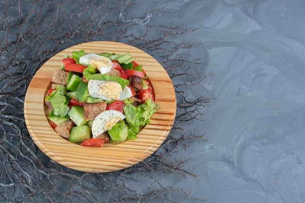 말린 된 빵 껍질과 대리석 배경에 플래터에 계란 추가와 셰퍼드 샐러드.