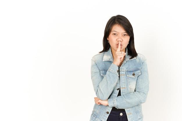 Shhは白で隔離のジーンズのジャケットと黒のシャツを着ている美しいアジアの女性の静かになります