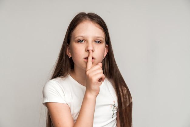 쉿, 조용히! 그녀의 입술에 손가락으로 침묵 제스처를 만드는 재미있는 귀여운 소녀의 초상화, 비밀, 어린이 신비를 유지합니다. 스튜디오 촬영에 고립 된 흰색 배경