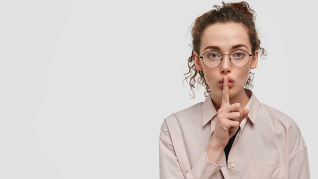 Shh, don`t make noise! attractive serious freckled woman with confident expression, shows hush gesture, asks to be silent, wears loose shirt and round glasses, stands over white wall with blank space