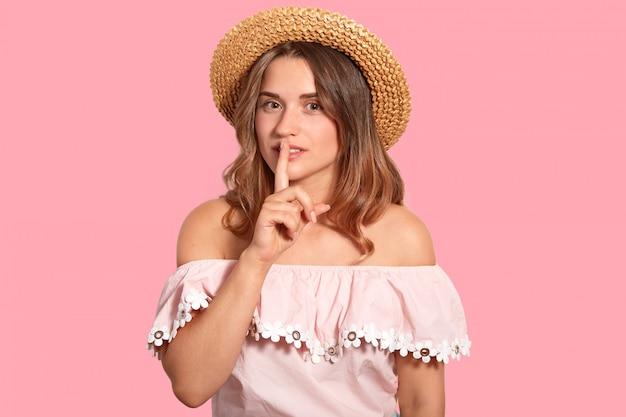 ああ、誰にもこれを言わないでください。秘密の女性は口に人差し指を置き、機密情報を伝え、麦わら帽子とファッショナブルなブラウスを着て、ピンクの壁にポーズをとります。静けさのコンセプト