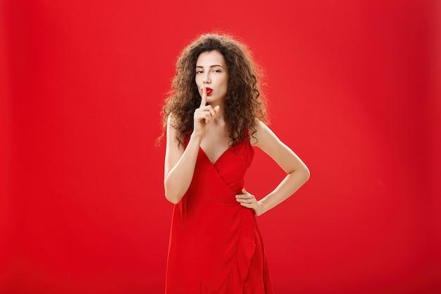 쉿, 우리 사이에 두자. 세련된 이브닝 드레스를 입은 매력적이고 우아한 성인 여성은 검지 손가락으로 입을 가리거나 빨간색 배경 위에 놀라움을 선사합니다.