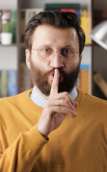 Shh, man secret finger. suspicious bearded man in glasses in office or apartment room looking at camera and brings his index finger to his mouth lips and she say shhh. close-up view