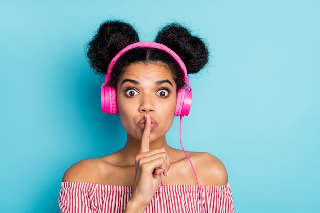 쉿! 내가 제일 좋아하는 노래! 재미 있은 어두운 피부 아가씨의 근접 촬영 사진 들어 음악 현대 이어폰 입술에 손가락을 잡고 빨간색 흰색 줄무늬 셔츠 오프 어깨 고립 된 파란색 벽을 착용