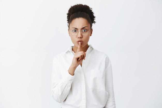 Shh, quiet, silence in class. strict and serious-looking dark-skinned female teacher in white-collar shirt and glasses making shush gesture with index finger over mouth, demanding keep voice down