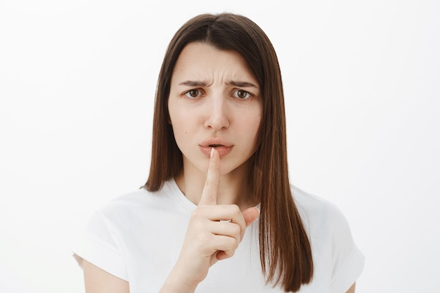 Shh you promise stay quiet. portrait of displeased and upset cute brunette in 20s frowning disappointed holding index finger over mouth as asking keep secret with shush gesture over gray wall
