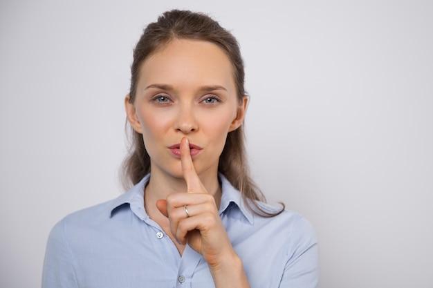 Shhのジェスチャーを示す謎めいた女性