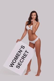 シーッ...灰色の背景に立っている間、ポスターを保持し、彼女の唇で人差し指を保持している魅力的な若い女性の全長