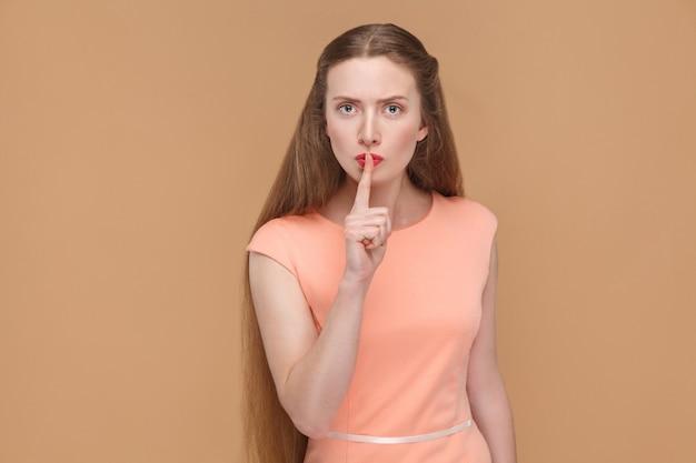 シーサイン、真面目な女性が指で唇に触れている。ピンクのドレスでメイクと長い髪の感情的なかわいい、美しい女性の肖像画。スタジオショット、ライトブラウンまたはベージュの背景に分離。