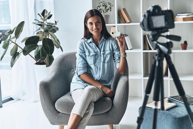Shiは専門家です。屋内で新しいビデオを作りながら美容製品を見せている魅力的な若い女性