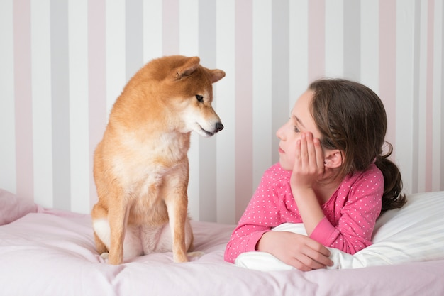 Shiba inu breed dog looking a little girl in her pajamas sitting on her pink bed