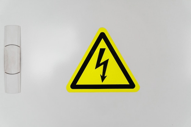A shield with a yellow triangle and a lightning bolt signifies high voltage