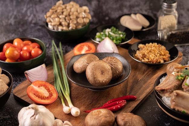 검은 시멘트 바닥에 마늘, 토마토, 고추, 파, 적 양파를 얹은 표고 버섯.